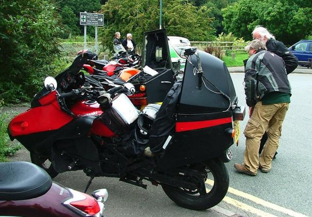 Camera mounted to left side of motorbike topbox you can operate by rewiring the headlamp flasher to take a still picture